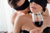 Fotografie Mann mit verbundenen Augen küsst Frau mit Glas Wein