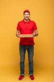 plná délka pohled na šťastný doručení muž v červené uniformě držení pizza box na žluté