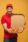 Fotografie glücklicher Lieferant in roter Uniform zeigt Schachtel mit leckerer Pizza isoliert auf gelb
