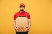 Fotografie Schockierter Zusteller in roter Uniform zeigt Schachtel mit leckerer Pizza