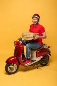 Fotografie šťastný dodávka muž v červené uniformě držení pizza boxy na skútru na žlutém pozadí
