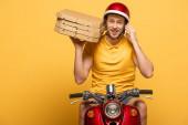 usmívající se dodávka muž ve žluté uniformě jezdecký skútr s krabicemi od pizzy a mluvit na smartphone izolované na žluté
