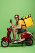 boční pohled na šťastný doručovatel ve žluté uniformě s batohem ukazující smartphone s prázdnou obrazovkou na skútru na zelené
