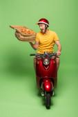 Fotografie šílený dodávka muž ve žluté uniformě na skútru doručující pizzu na zelené