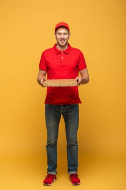 full length view of happy delivery man in red uniform holding pizza box on yellow