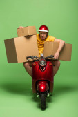 tired delivery man in yellow uniform on scooter with boxes on green