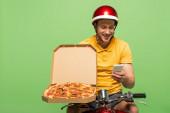 Fotografie usmívající se dodávka muž ve žluté uniformě na skútru s pizzou pomocí smartphone izolované na zelené