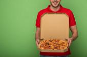oříznutý pohled na usmívajícího se doručovatele v červené uniformě držící krabici od pizzy na zelené