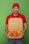 Fotografie glücklicher Zusteller in roter Uniform mit Pizzakarton auf grünem Grund