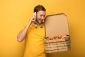 šťastný muž se sluchátky ve žlutém oblečení drží pizzu a mluví na smartphone na žlutém pozadí