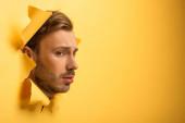 trauriger schöner Mann mit Kopf in gelbem Papierloch