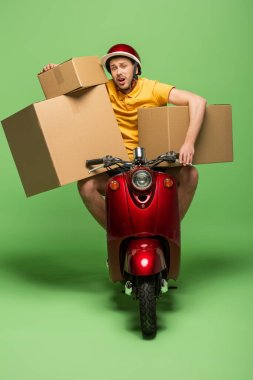 Exhausted delivery man in yellow uniform on scooter with boxes on green stock vector