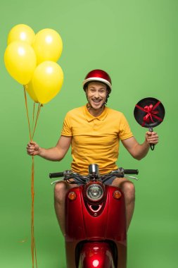 Happy delivery man in yellow uniform on scooter with frying pan and balloons isolated on green stock vector