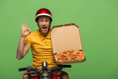 Winking delivery man in yellow uniform on scooter with pizza showing ok sign isolated on green stock vector