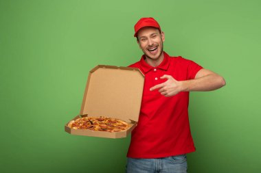 happy delivery man in red uniform pointing with finger at pizza box on green