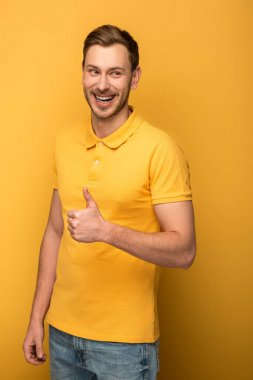 Happy handsome man in yellow outfit showing thumb up on yellow background stock vector