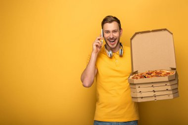 happy man with headphones in yellow outfit holding pizza and talking on smartphone on yellow background