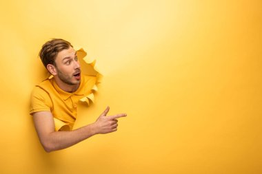 crazy handsome man in yellow outfit in yellow paper hole pointing with finger aside