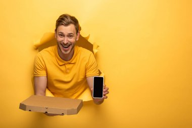 Happy handsome man in yellow outfit holding smartphone and pizza box in yellow paper hole stock vector