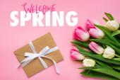 Horní pohled na obálku s lukem a kyticí tulipánů na růžovém povrchu, vítejte jarní ilustrace