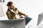 Vysokoúhlý pohled na digitální návrháře popíjejícího kávu v blízkosti počítačů a grafických tabletů na stole