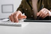 Selektivní zaměření digitálního designéra pomocí počítačové klávesnice a grafického tabletu na stůl