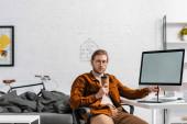 Komplexní digitální designér s papírovým kelímkem s perem v blízkosti grafického tabletu a počítačem na stole