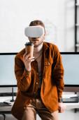 Digitální návrhář ve sluchátkách virtuální reality držící papírový kelímek poblíž počítačových monitorů na stole