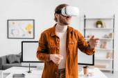Usmívající se 3D umělec gestikulace při použití virtuální reality headset v kanceláři