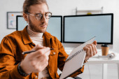 Selektivní zaměření pohledného digitálního designéra držícího pero a notebook v kanceláři