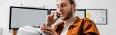 Panoramatický záběr digitální designérky mluvící na smartphonu a držící v kanceláři sluchátka virtuální reality