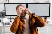 Vyčerpaný 3D designér mluví na smartphone v kanceláři