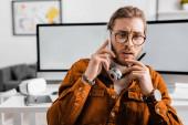 Pensive 3D umělec drží stylus grafického tabletu a mluví na smartphone v kanceláři