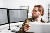 Selektivní zaměření pohledného digitálního designéra, který drží plán a prohlíží si počítačové monitory na stole
