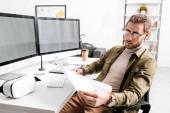 Digitális tervező vizsgálja tervrajz, miközben teszi projekt 3D-s design számítógépek asztalnál