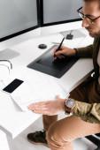 Jóképű digitális tervező tervrajzot használ, miközben grafikus táblagéppel és számítógépekkel dolgozik a vr headset közelében az asztalon