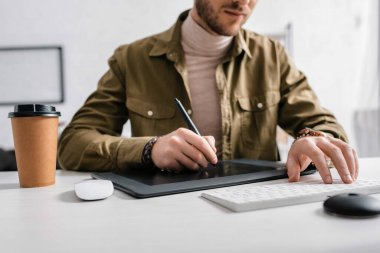 Cropped view of 3d artist using graphics tablet and computer keyboard near coffee to go on table stock vector