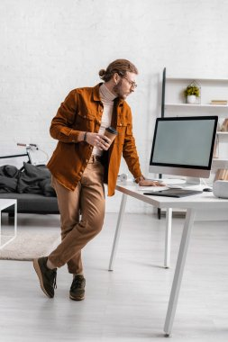 Handsome 3d artist holding coffee to go and looking at computer monitor on table in office stock vector