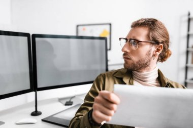 Selective focus of handsome digital designer holding blueprint and looking at computer monitors on table stock vector
