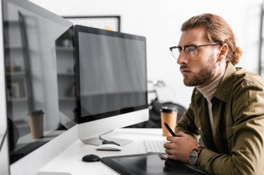 Side view of handsome 3d artist holding stylus near graphics tablet and looking at computer monitors with blank screen on table stock vector