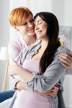 Smiling woman hugging positive girlfriend in bedroom stock vector