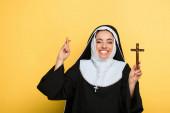 vidám apáca tartja kereszt közben mutató ujjak keresztbe sárga
