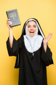 Photo beautiful excited nun holding holy bible on grey