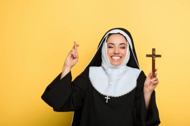 Cheerful nun holding cross while showing fingers crossed on yellow stock vector