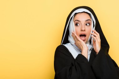 Beautiful surprised nun talking on smartphone isolated on yellow stock vector