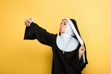 Beautiful nun with air kiss taking selfie on smartphone isolated on yellow stock vector