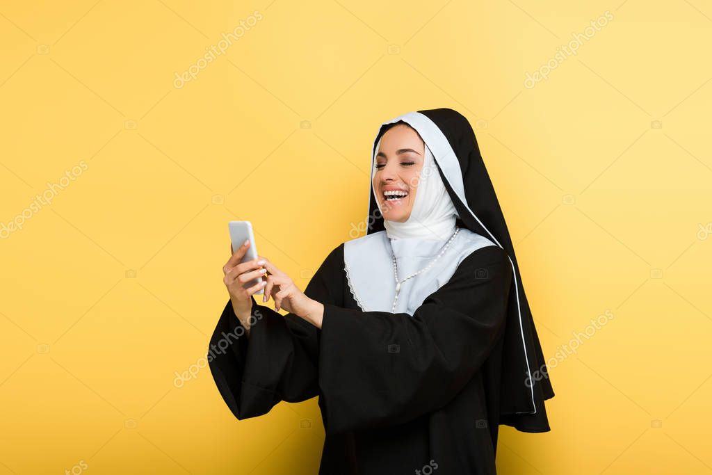 Beautiful excited nun using smartphone on yellow stock vector