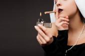 Fotografie Ausgeschnittener Blick auf Nonne, die Marihuana-Joint mit Feuerzeug raucht