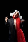 emotionale sexy dämonische Nonne hält Dollar-Banknote und Smartphone mit Kokainlinien isoliert auf schwarz