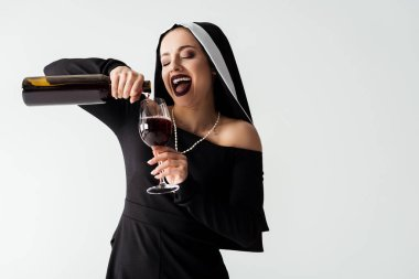 Excited sexy nun pouring wine from bottle into glass isolated on grey stock vector